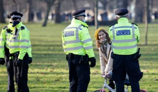 Police officers talk with a family as they patrol in Clapham Common, south London.