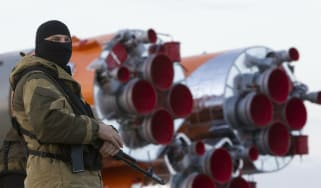 A Russian solider stands guard over the Soyuz TMA-14M spacecraft