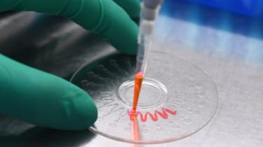 A technician demonstrating how to inject a nucleic acid sample onto a disk for analysis, in a lab
