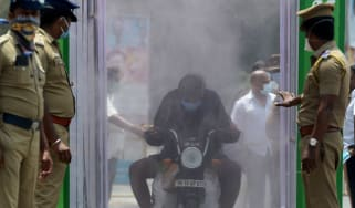 A motorcyclist rides through a disinfection tunnel in Chennai