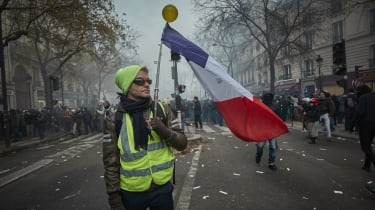 PARIS, FRANCE - DECEMBER 05: A Gilet Jaune, or Yellow Vest' holds a French Tricolor amidst tear gas as protestors and French Riot Police clash during a rally near Place de Republique in suppo