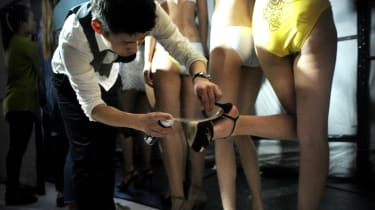 A model (R) prepares backstage before the Hosa Swimming Fashion Trend Show during China Fashion Week in Beijing on March 28, 2014. China Fashion Week runs from March 24 to 31.AFP PHOTO / WANG