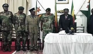 Robert Mugabe, flanked by Zimbabwe Defence Force officers, prepares for his TV address