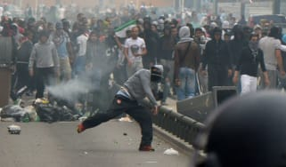A pro-Palestinian protester throws a projectile at a French police officer