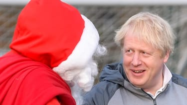 Boris Johnson speaks with a man dressed as Father Christmas in 2019