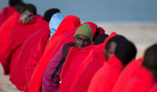 Migrants keep warm with Red Cross blankets upon their arrival at Malaga harbour this year