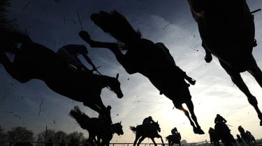 CHELTENHAM, ENGLAND - MARCH 13:Runners and riders jump the third last in the Fulke Walwyn Kim Muir Challenge Cup Handicap Chase at Cheltenham Racecourse on March 13, 2014 in Cheltenham, Engla