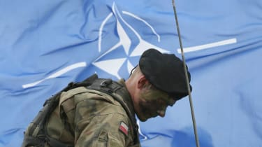 A Polish solider in front of a Nato flag