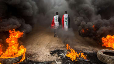 TOPSHOT - Anti-government protesters draped in Iraqi national flags walk into clouds of smoke from burning tires during a demonstration in the southern city of Basra on November 17, 2019, as