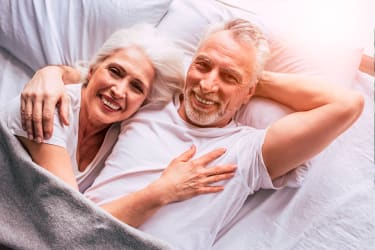 Older woman and man cuddling in bed