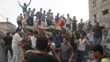 Palestinians carry the body of a woman killed in an Israeli air strike