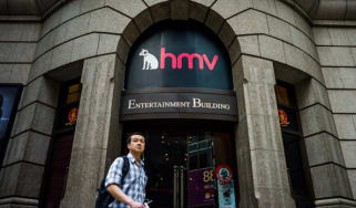 A man walks past a building housing a HMV store in Hong Kong on January 17, 2013. Iconic British music retailer HMV is fighting for survival after slumping into administration, but its boss e