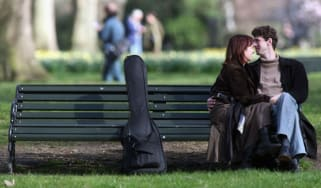 A couple sit on a bench in St James's Park in London