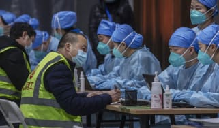 Chinese workers wait to receive a COVID-19 vaccine jab