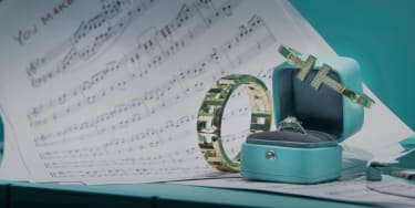 Two Tiffany bangles and a ring in a turquoise box on top of some sheet music