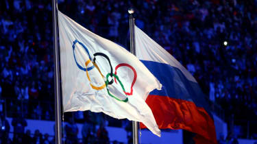The Olympic flag and Russian flag are raised at the 2014 Sochi Winter Olympics closing ceremony