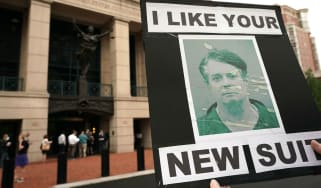 Protesters hold a poster of Paul Manafort outside court