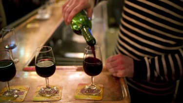 A waiter serves glasses of red wine at the counter of a bar on December 2, 2011 in Paris. AFP PHOTO / FRED DUFOUR(Photo credit should read FRED DUFOUR/AFP/Getty Images)