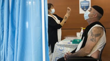 A patient awaits a vaccine jab at a mass vaccination centre in Tel-Aviv