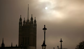 The sun shines through clouds over the Palace of Westminster.