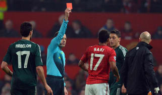 Turkish referee Cuneyt Cakir (2L) shows Manchester United's Portuguese midfielder Nani (3R) the red card to send him off during the UEFA Champions League round of 16 second leg football match