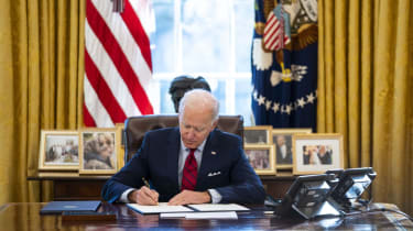 Joe Biden signs an executive order at the Resolute Desk in the Oval Office