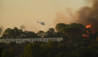 A firefighting helicopter flies above a wildfire near the Château des Bertrands winery in the Var region of Provence, France