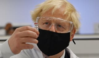 Boris Johnson poses with a vial of the Oxford-AstraZeneca vaccine