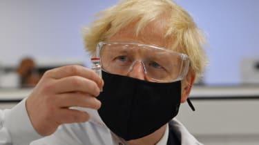 Boris Johnson poses with a vial of the Oxford-AstraZeneca vaccine