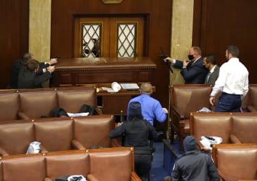 Capitol police officers point their guns at a door that was vandalized in the House Chamber.