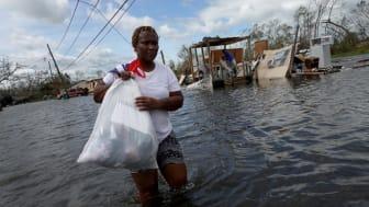 Woman walks through flooded street in Louisana