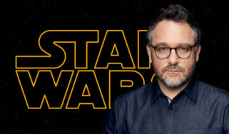 Colin Trevorrow in front of the Star Wars logo