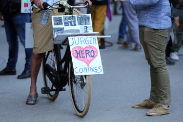 A cyclist displays a sign in support of Jurgen Conings