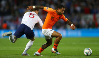 England defender John Stones loses the ball to Holland's Memphis Depay