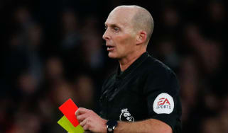 Referee Mike Dean shows a red card during a Premier League fixture