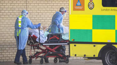NHS workers in PPE transport a patient