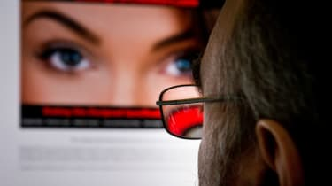 A man looks at hacked dating website Ashley Madison
