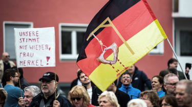 AfD supporters in Essen carry a sign saying, 'Never our voice again, Mrs Merkel'