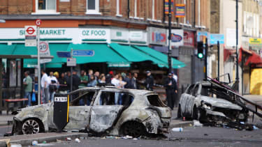 Burnt out cars lie in the road after riots in Tottenham