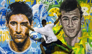 Youngsters play football in front of a World Cup mural in a Rio favela