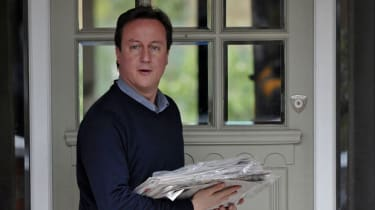 British opposition Conservative party Leader David Cameron returns to his home, after leaving to buy newspapers, in west London on May 09, 2010.Cameron stands on the brink of finally becoming