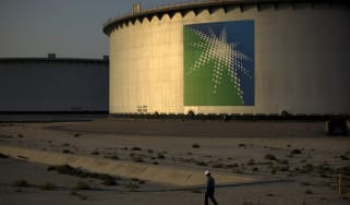 An employee walks past crude oil storage tanks at the Juaymah Tank Farm in Saudi Aramco's Ras Tanura oil refinery and oil terminal in Ras Tanura, Saudi Arabia, on Monday, Oct. 1, 2018. Saudi