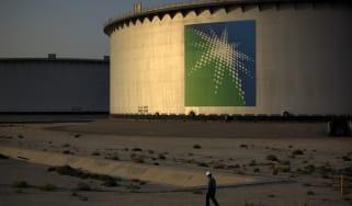 An employee walks past crude oil storage tanks at the Juaymah Tank Farm in Saudi Aramco's Ras Tanura oil refinery and oil terminal in Ras Tanura, Saudi Arabia, on Monday, Oct. 1, 2018. Saudi