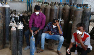 People wait to get their oxygen cylinders filled in Bengaluru, India