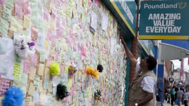 Notes are pinned on a 'peace wall' on a boarded-up window of Poundland