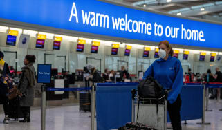 A passenger pushes her bags through Heathrow Airport