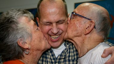 Al-Jazeera journalist Peter Greste is kissed by his mother Lois (L) and father Juris (R) upon his arrival at Brisbane's international airport in the early hours of February 5, 2015.Greste arr