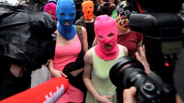 Wearing masks members of Russian punk group Pussy Riot, Nadezhda Tolokonnikova (L) and Maria Alyokhina (R) speak to journalists while leaving the police station of Adler, near Sochi, on Febru