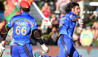 Afghanistan batsman Shapoor Zadran celebrates with teammate Hamid Hassan after hitting the winning runs to defeat Sco