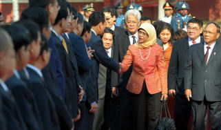 Halimah Yacob shakes hands with members of Singapore's parliament